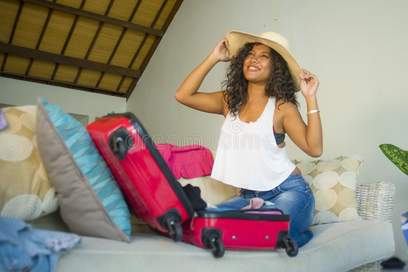 La mujer afroamericana negra feliz atractiva y loca joven en el sombrero del verano de la playa que prepara la maleta que se va p fotos de archivo