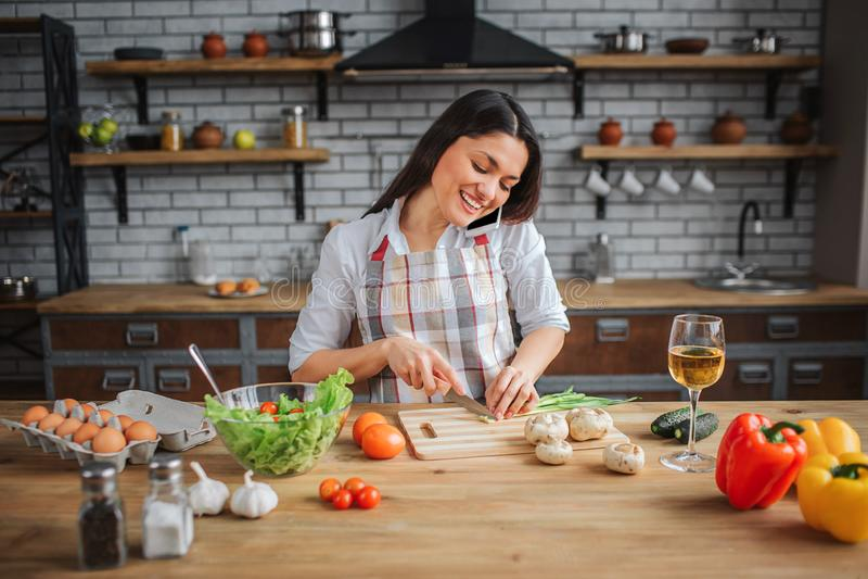 La mujer agradable alegre se sienta en la tabla en cocina Ella cortó la cebolla verde y la charla sobre el teléfono Mirada modelo imagen de archivo libre de regalías
