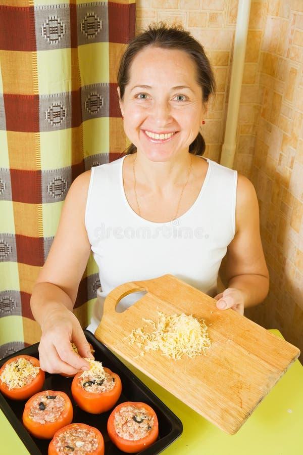 La mujer agrega el queso al tomate relleno fotos de archivo libres de regalías