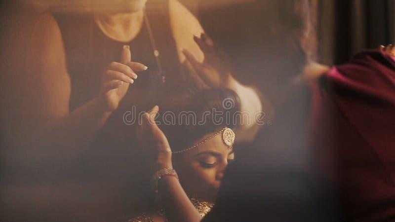 La mujer ajusta maquillaje en la cara de la novia imponente mientras que ella sienta calma en la silla almacen de metraje de vídeo