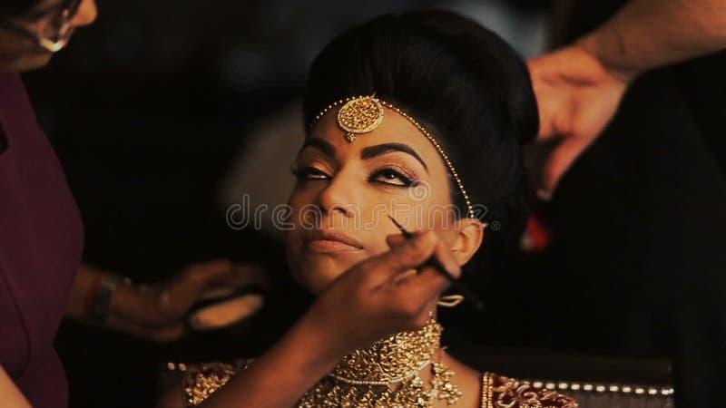La mujer ajusta maquillaje en la cara de la novia imponente mientras que ella sienta calma en la silla metrajes