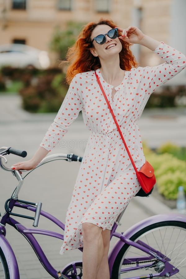 La mujer alegre activa monta la bicicleta en ciudad, lleva las gafas de sol elegantes, hace la sonrisa encantadora dentuda, vesti imagen de archivo libre de regalías