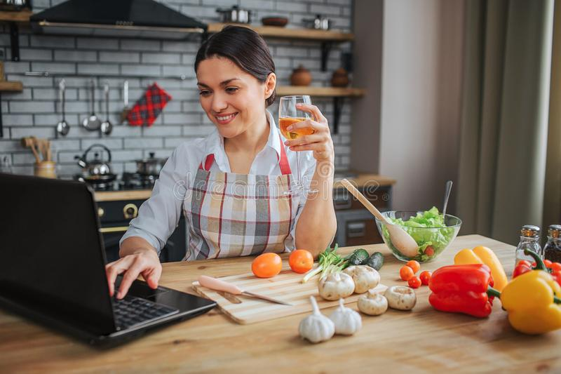 La mujer alegre agradable se sienta en la tabla en cocina Ella mecanografía en el ordenador portátil y la sonrisa del teclado Vid fotos de archivo