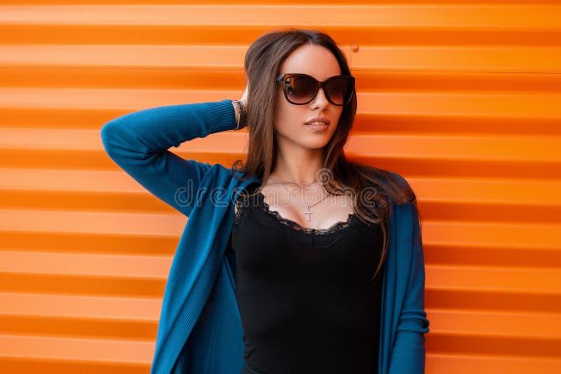 La mujer alegre bonita joven del inconformista con una sonrisa en un vintage hizo punto el cabo azul en gafas de sol de moda en u fotografía de archivo libre de regalías