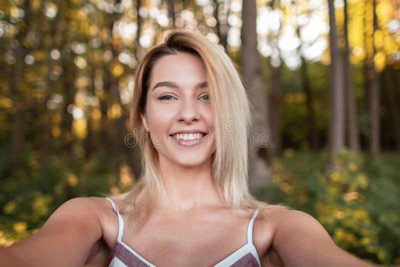 La mujer alegre bonita joven en un vestido rosado de moda hace el selfie en un teléfono en el bosque entre los árboles en un día  foto de archivo