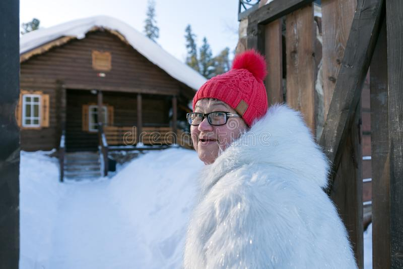 La mujer alegre camina en la puerta y va en dirección de una casa de madera rústica imágenes de archivo libres de regalías