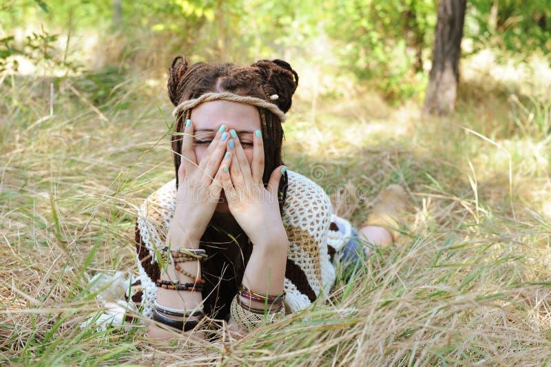 La mujer alegre del estilo del indie con el peinado de los dreadlocks, se divierte que se cierra la cara con las manos fotografía de archivo libre de regalías
