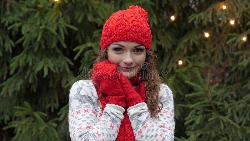 La mujer alegre en el sombrero de Papá Noel con la bufanda y las manoplas rojas es feliz y de salto contra la perspectiva del árb fotografía de archivo libre de regalías
