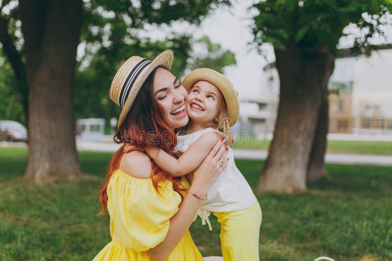 La mujer alegre en ropa amarilla juega en césped de la hierba verde en parque para divertir y abrazar, abrace con poco bebé lindo foto de archivo libre de regalías