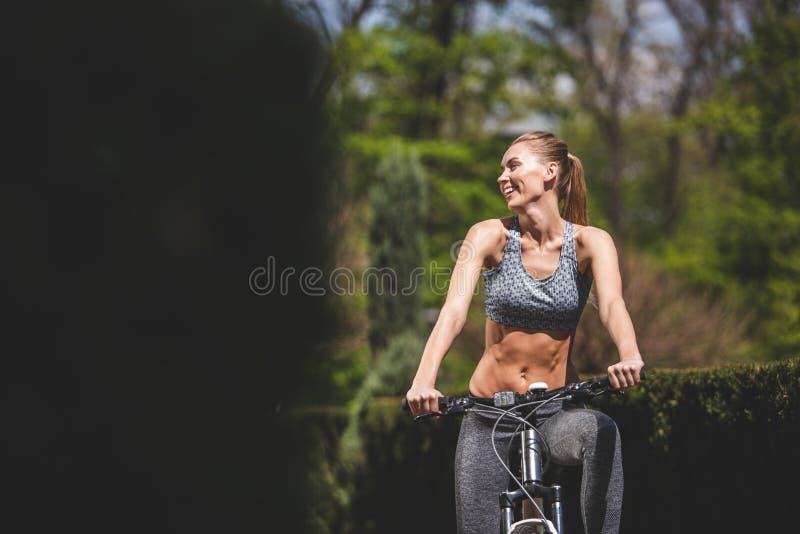La mujer alegre está completando un ciclo entre céspedes foto de archivo