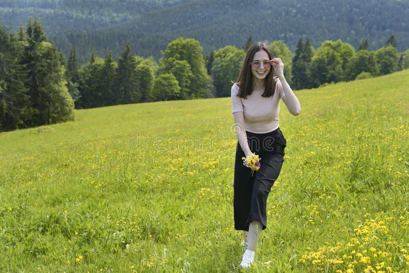 La mujer alegre joven está caminando en un prado de la flor Verano d soleada imágenes de archivo libres de regalías