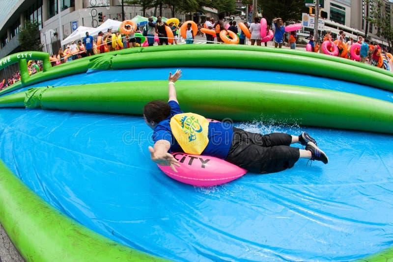 La mujer alegre monta el tobogán acuático gigante del tubo interior abajo en Atlanta imagen de archivo