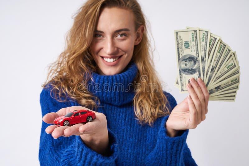 La mujer alegre ofrece comprar un coche foto de archivo