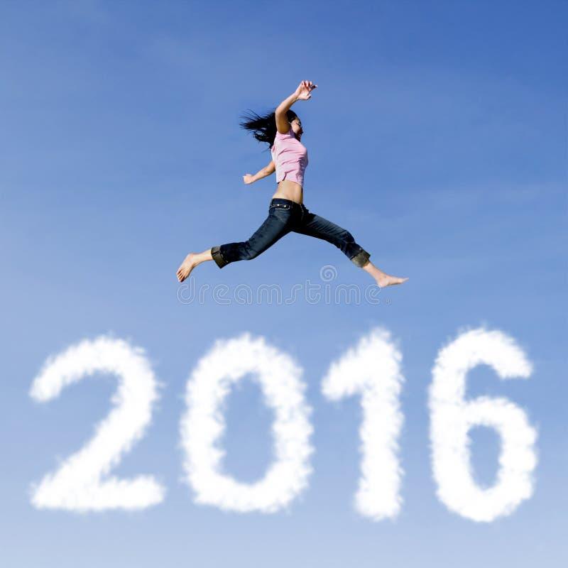 La mujer alegre salta sobre los números 2016 imagen de archivo