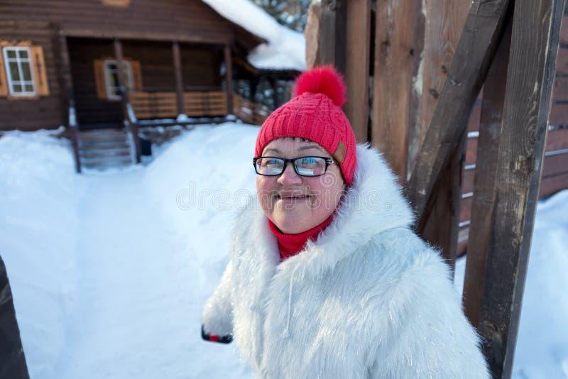 La mujer alegre se coloca en la entrada de la casa de madera del pueblo imagen de archivo