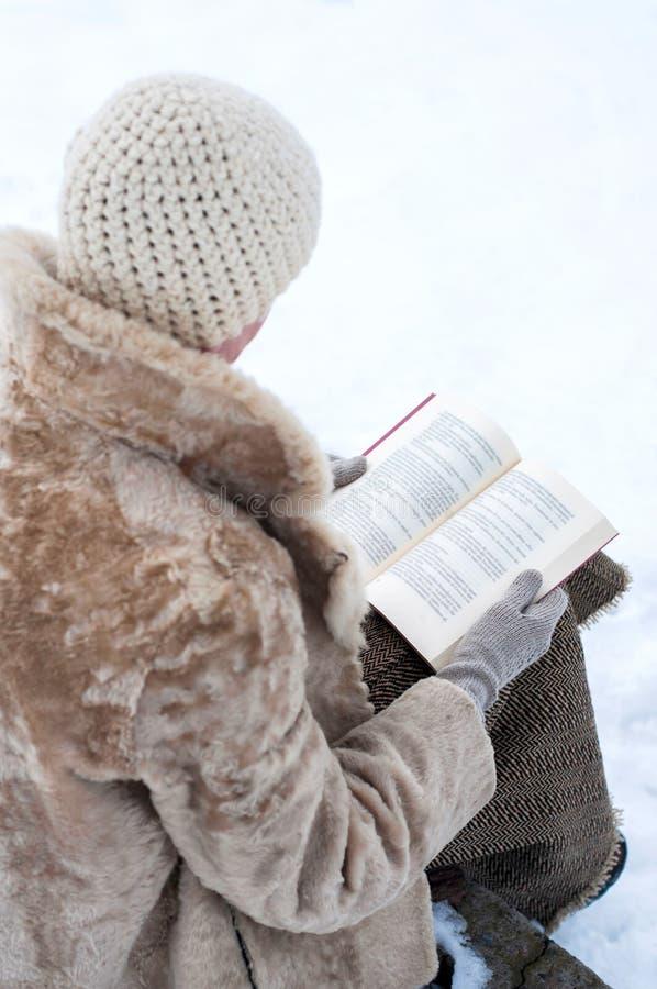 La mujer alista un libro en invierno imágenes de archivo libres de regalías
