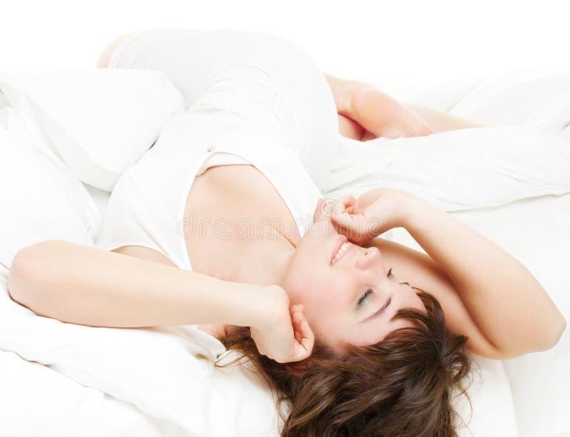 La mujer animada se está relajando en la cama imagen de archivo libre de regalías