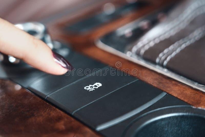 La mujer apaga el modo de deslizamiento en el tablero de mandos del automóvil fotografía de archivo libre de regalías
