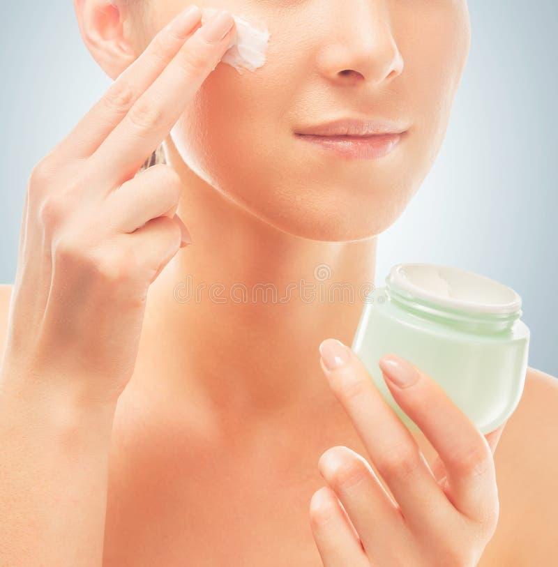 La mujer aplica la crema en la cara, primer foto de archivo libre de regalías