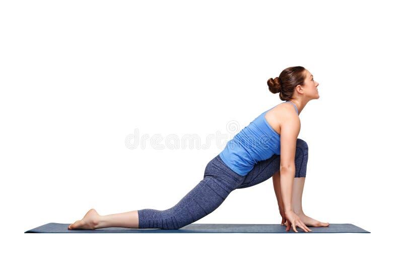 La mujer apta del yogini practica el asana Anjaneyasana de la yoga foto de archivo