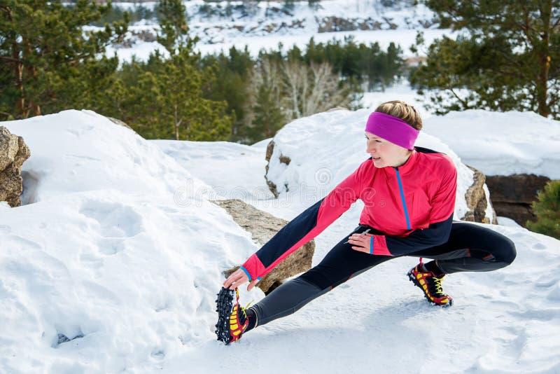 La mujer apta que hace estirar ejercita antes de correr al aire libre Entrenamiento de la calle del invierno imagen de archivo libre de regalías