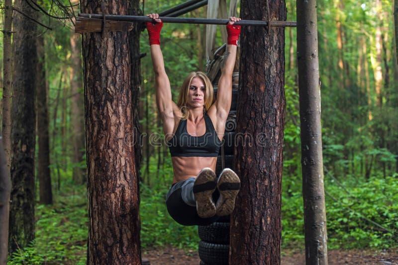 La mujer apta que hace la pierna de la ejecución levanta los músculos del ABS ejercita en la barra horisontal que se resuelve afu imágenes de archivo libres de regalías