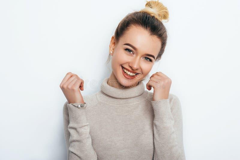 La mujer apuesta joven alegre con el bollo adorable del pelo de la sonrisa que presentaba en blanco aisló el fondo sonrisa amplia imagenes de archivo