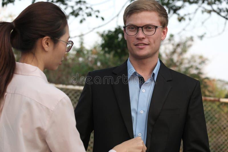 La mujer arregla la camisa del hombre de negocios y se adapta a al aire libre ajuste de la novia fotografía de archivo libre de regalías