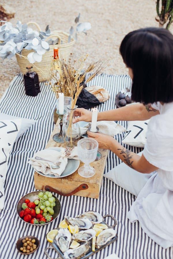 La mujer arregla decoraciones de la comida campestre de la boda foto de archivo