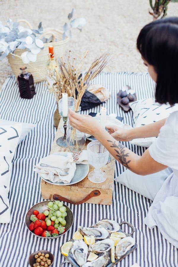 La mujer arregla decoraciones de la comida campestre de la boda imagen de archivo