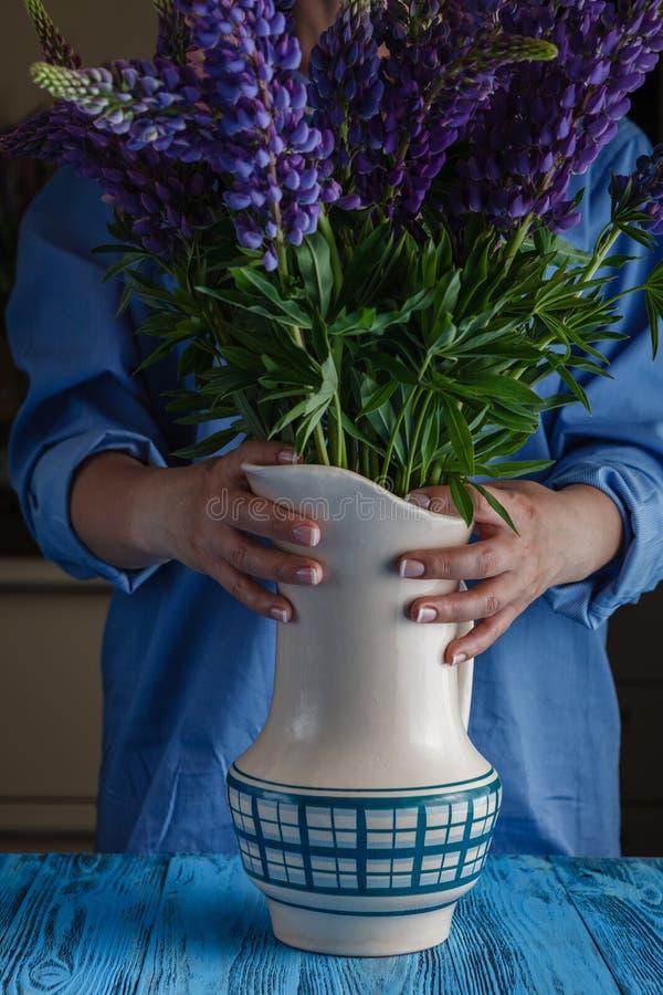 La mujer arregla el ramo de la flor de la primavera en un florero fotos de archivo libres de regalías
