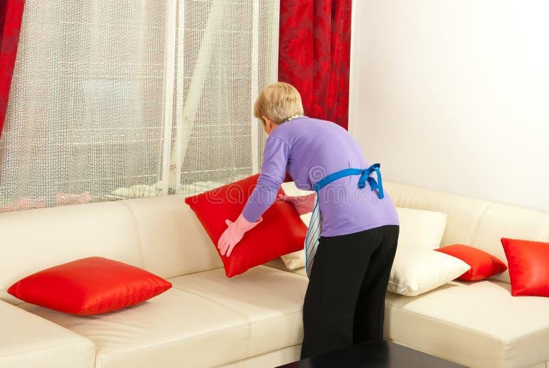 La mujer arregla las almohadillas en el sofá foto de archivo