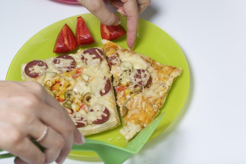 La mujer arregla la pizza cocinada de la pasta de hojaldre sobre las placas foto de archivo libre de regalías