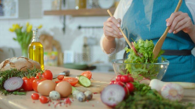 La mujer ascendente cercana está cocinando la ensalada fresca en la cocina imagen de archivo libre de regalías