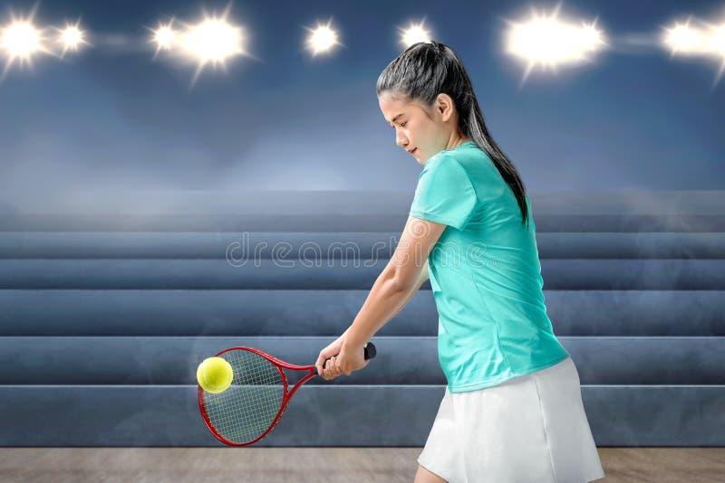 La mujer asiática con una estafa de tenis en sus manos golpeó la bola fotografía de archivo libre de regalías
