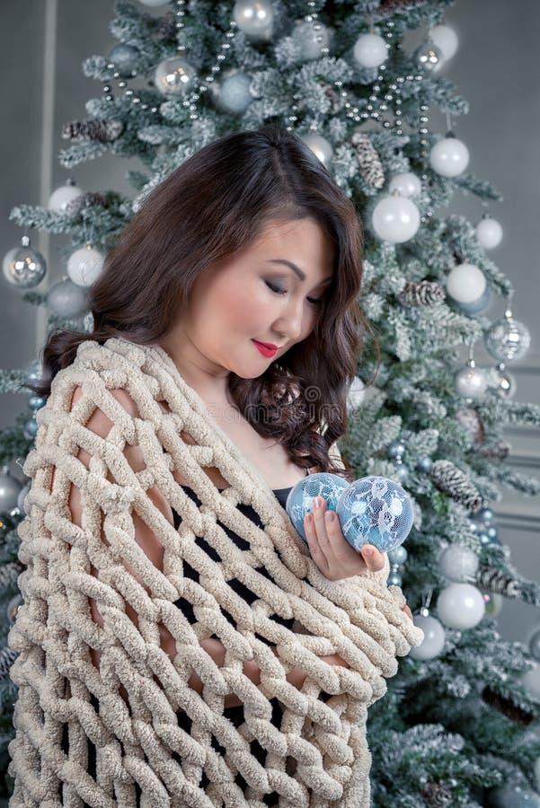 La mujer asiática contra el árbol de navidad sostiene bolas de la Navidad fotografía de archivo libre de regalías