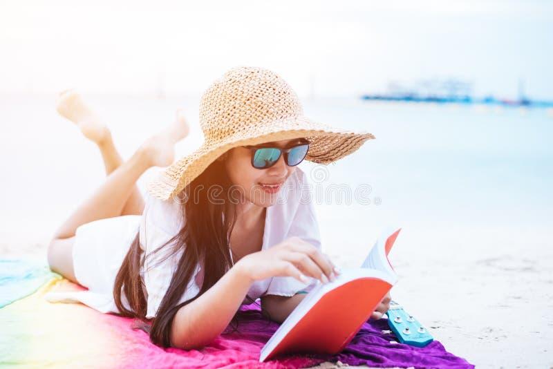 La mujer asiática de la belleza tiene vacaciones en la playa Sombrero del ala de la muchacha y libro de lectura que llevan en la  fotografía de archivo libre de regalías