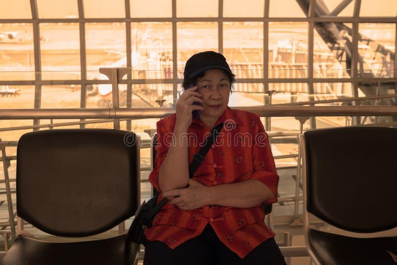 La mujer asiática del elser maduro está invitando a un teléfono celular imagen de archivo libre de regalías