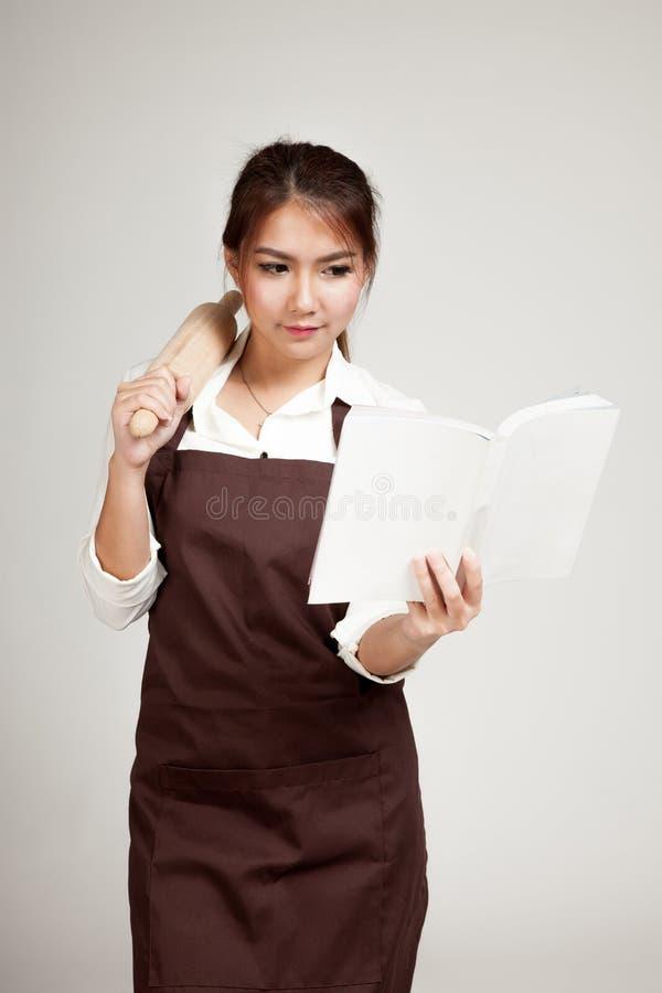 La mujer asiática del panadero en delantal con el rodillo de madera y el cocinero reservan imágenes de archivo libres de regalías