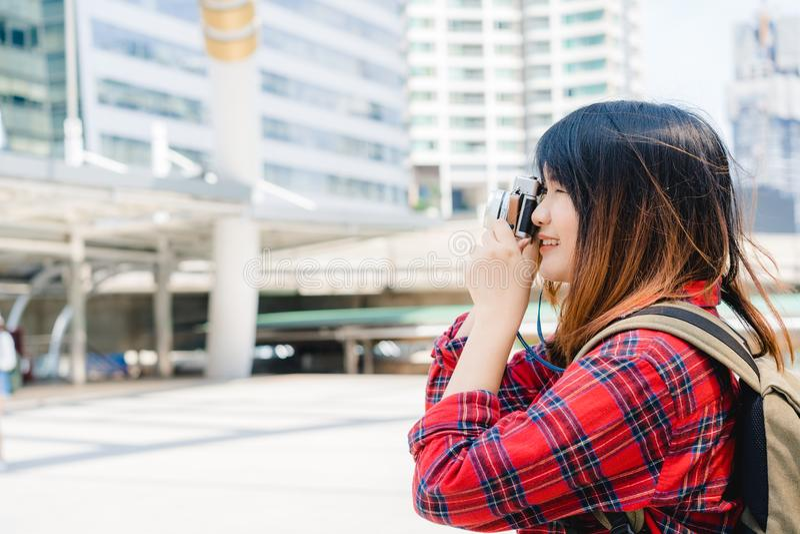 La mujer asiática del viajero hermoso feliz lleva la mochila Las mujeres asiáticas alegres jovenes que usan la cámara a hacer la  foto de archivo