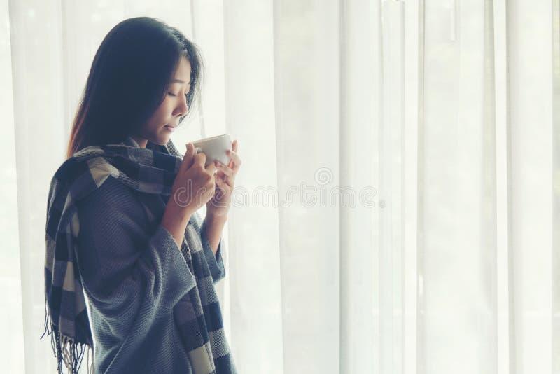 La mujer asiática en café de consumición del dormitorio después de despierta cerca de la ventana, mañana soleada, fotografía de archivo