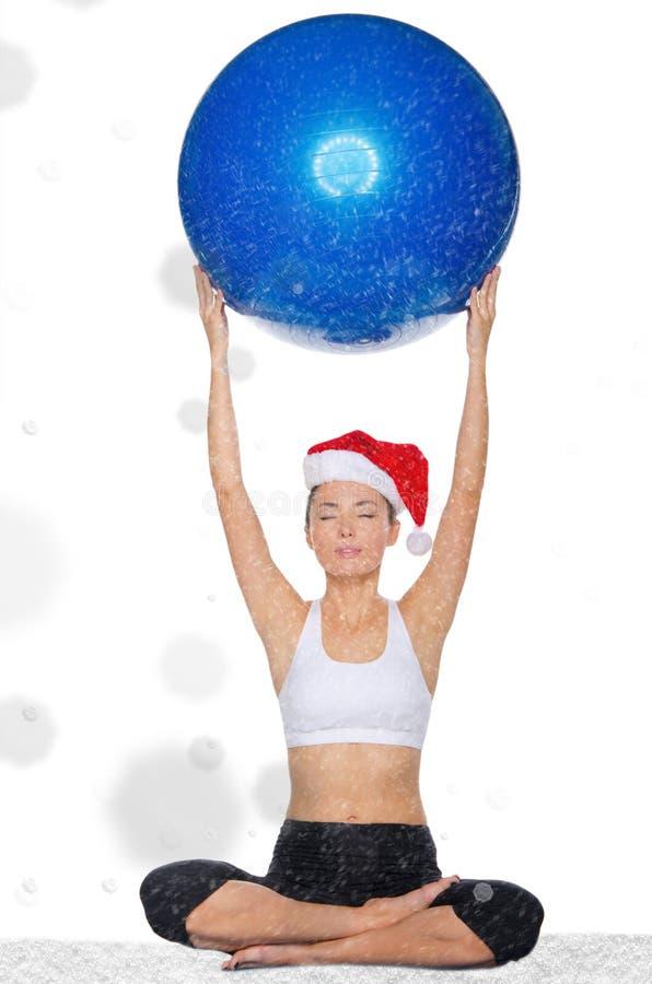 La mujer asiática en casquillo de la Navidad lleva a cabo el undersnow de las bolas de los pilates foto de archivo libre de regalías