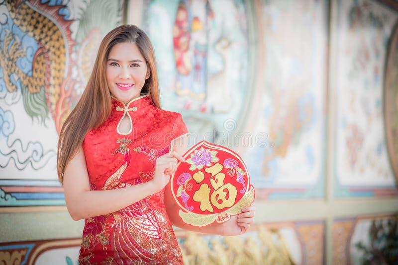 La mujer asiática en chino viste sostener el pareado 'feliz' (lomo imagenes de archivo