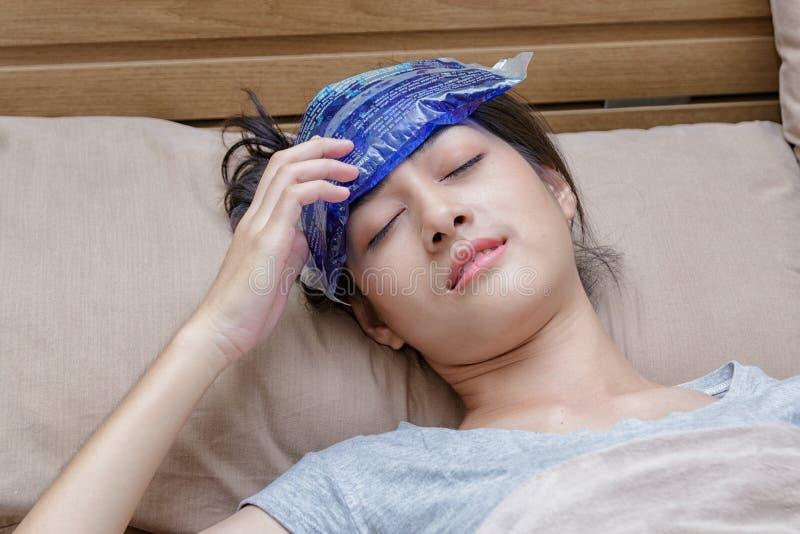 La mujer asiática enferma cogió frío y fiebre o dolor de cabeza y mentira imagen de archivo