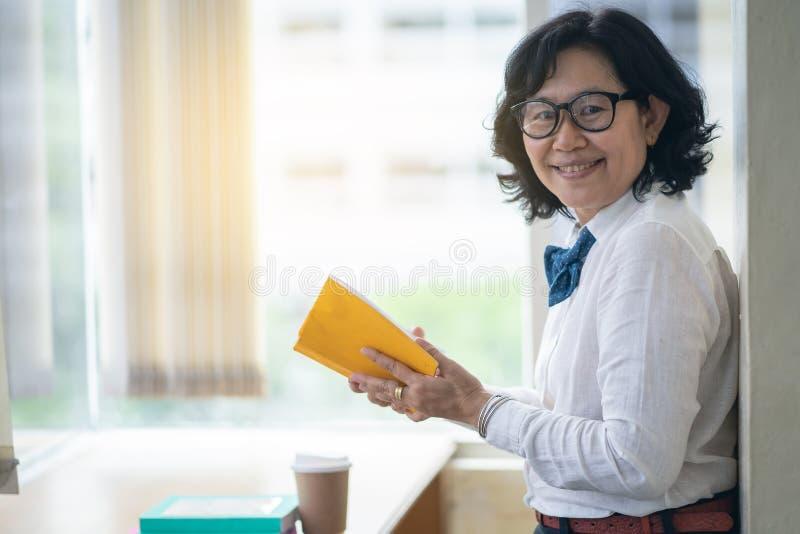 La mujer asiática es feliz en biblioteca imagen de archivo libre de regalías