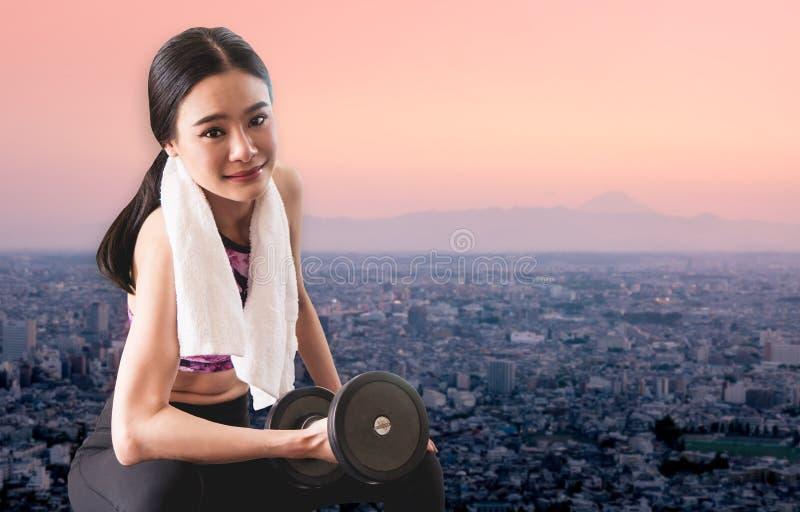 La mujer asiática está levantando pesa de gimnasia con la ciudad de Tokio imagen de archivo libre de regalías