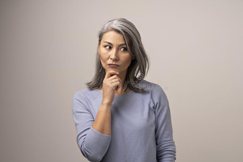 La mujer asiática está tocando su pensamiento de la barbilla fotografía de archivo libre de regalías