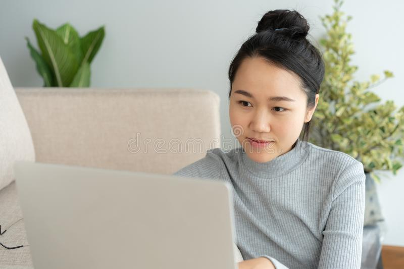 La mujer asiática está trabajando en un ordenador portátil en sala de estar Ella se sienta en el piso y el sofá es escritorio de  fotografía de archivo