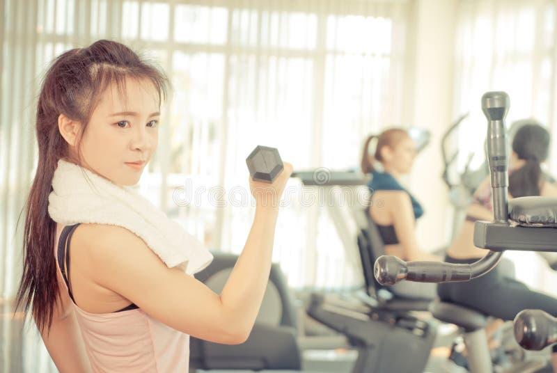 La mujer asiática fuerte está levantando pesa de gimnasia en aptitud fotografía de archivo