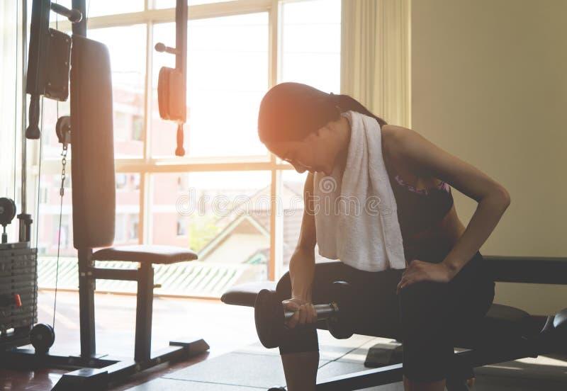 La mujer asiática fuerte está levantando pesa de gimnasia en aptitud imagen de archivo libre de regalías